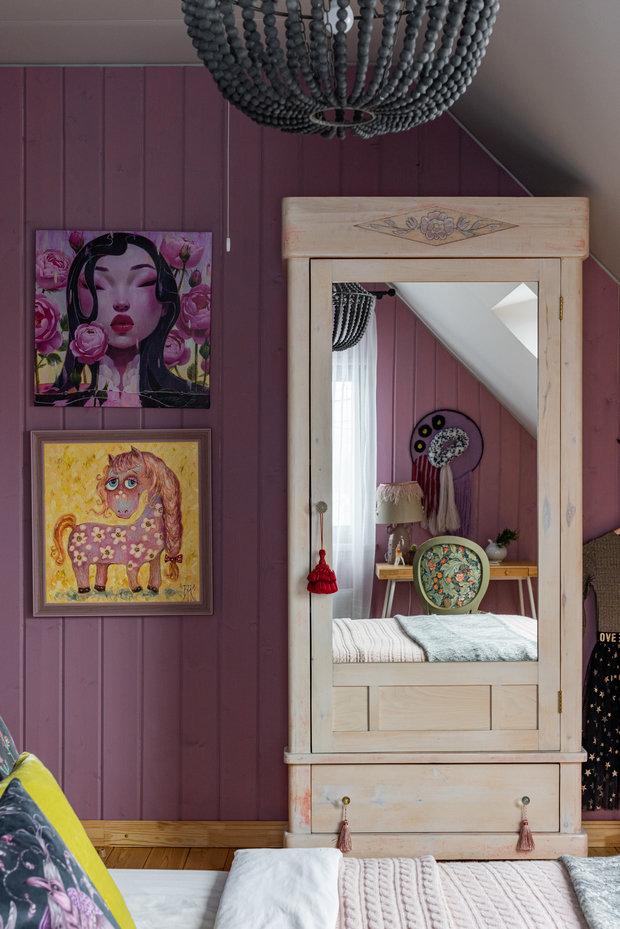 Цветовая гамма этой комнаты насыщенная — лиловый цвет контрастирует с натуральной неокрашенной фактурой дерева. Главный герой этого кадра — отреставрированный шкаф 50-х годов из массива березы. Он интересен тем, что на нем достаточно много деталей, а для мебели того времени это редкость.