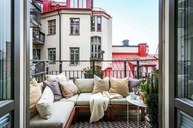 Как сделать пространство открытого балкона более приватным? Помогут диван или софа, развернутые спинкой наулицу. Анаперила повесьте кашпо срастениями.