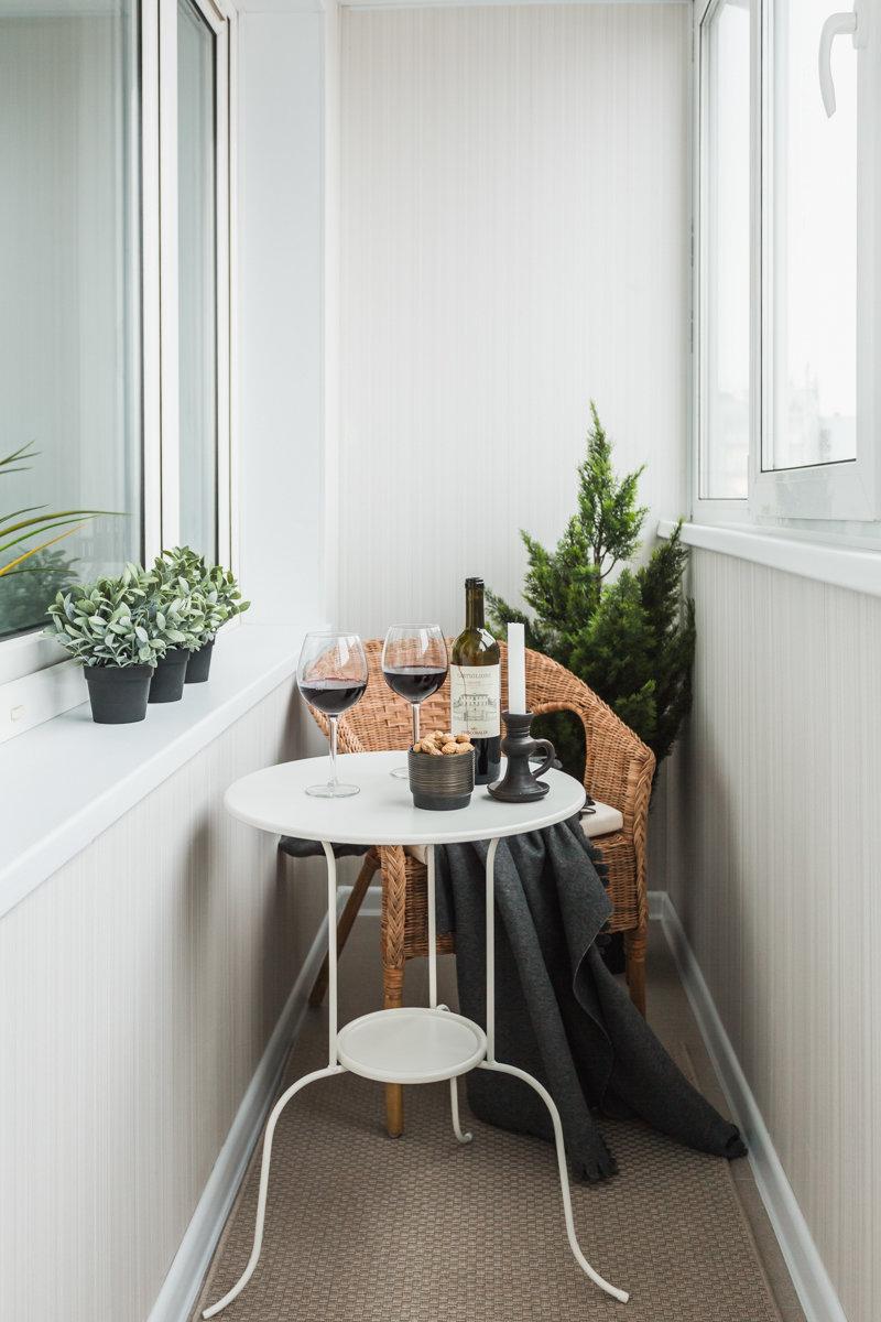 Балкон в белом цвете. узкий балкон со столиком и креслом. бю.