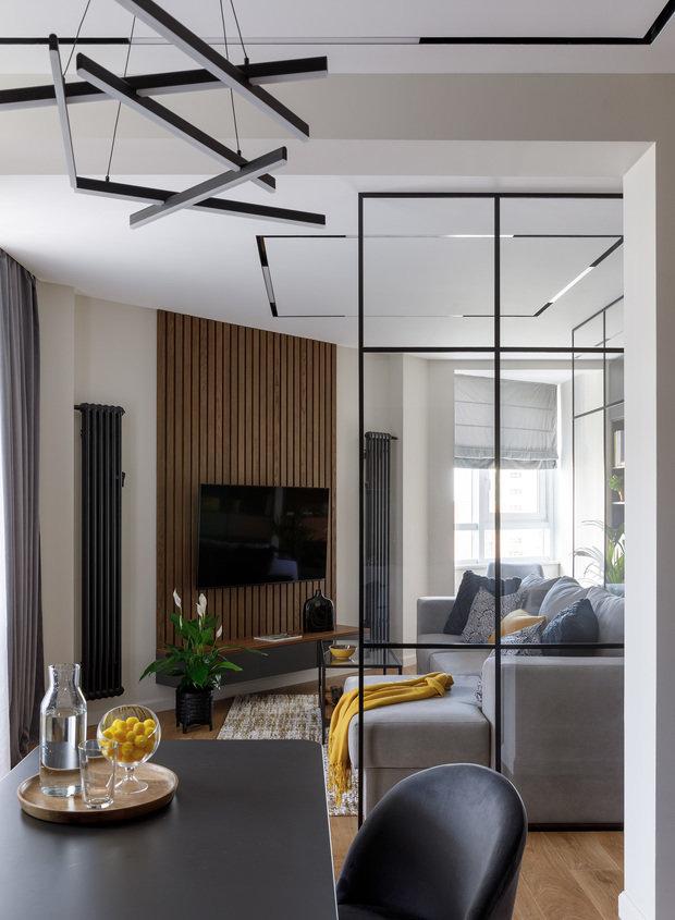 В интерьере все детали перекликаются между собой: черная межкомнатная перегородка, встроенный свет на потолке, дизайн люстры над обеденным столом.