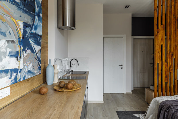 Отделить зону прихожей от комнаты позволила декоративная деревянная перегородка: она также немного скрыла спальню от просмотра из зоны входной двери.