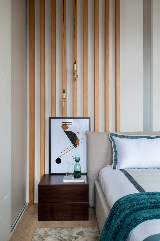 В отделке спальни использовали рейки натурального цвета дерева и обои.