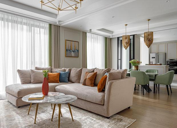 Общая цветовая гамма — спокойные светлые тона. Зона гостиной выходит на солнечную сторону, тут всегда много света. Дизайнеры усилили эффект и поддержали цветовыми акцентами: зеленым в текстиле для стульев и теплым оранжевым в качестве дополнительного оттенка.