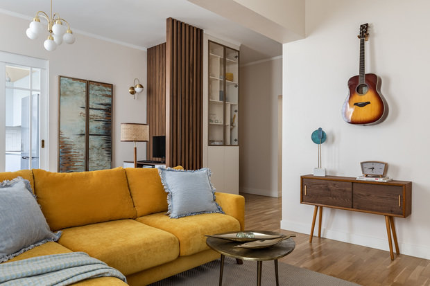 Дизайнеры сделали ставку на игру контрастов: холодных и теплых тонов, современных деталей — с винтажной мебелью. А доминантой композиции в гостиной стал желтый диван, который даже в зимнее время будет делать квартиру теплой и уютной.