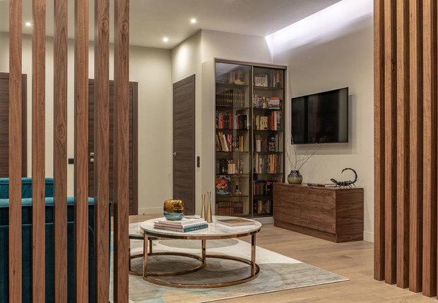 В гостиной обилие дверей и дерева, но все смотрится гармонично за счет правильно подобранных оттенков.