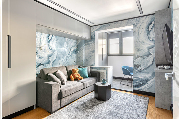 Обои с волнами создают очень уютную атмосферу в комнате сына.