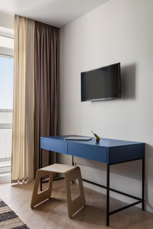 Помимо обеденной группы в квартире-студии удалось расположить письменный стол, выполненный на заказ в синем цвете в поддержку кухне-нише.