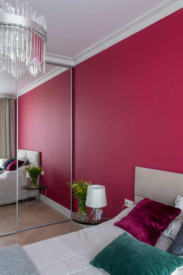 Акцентную стену за кроватью выделили активным ягодным оттенком.