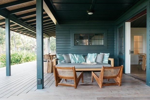 Диван для гостиной на открытом воздухе разработан специально и гармонирует с угловатыми тиковыми стульями Пьера Жаннере.