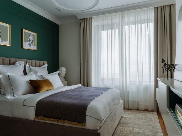 В спальне на стену за изголовьем кровати добавили изумрудный цветовой акцент.