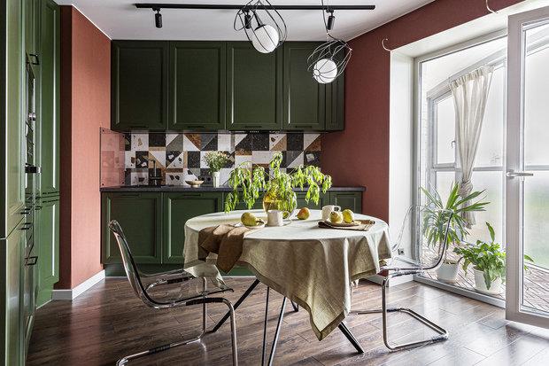 Цвета очень насыщенные: терракотовые стены, темный гарнитур сложного зеленого оттенка. Внимание обращает на себя пестрый фартук с красивой раскладкой.