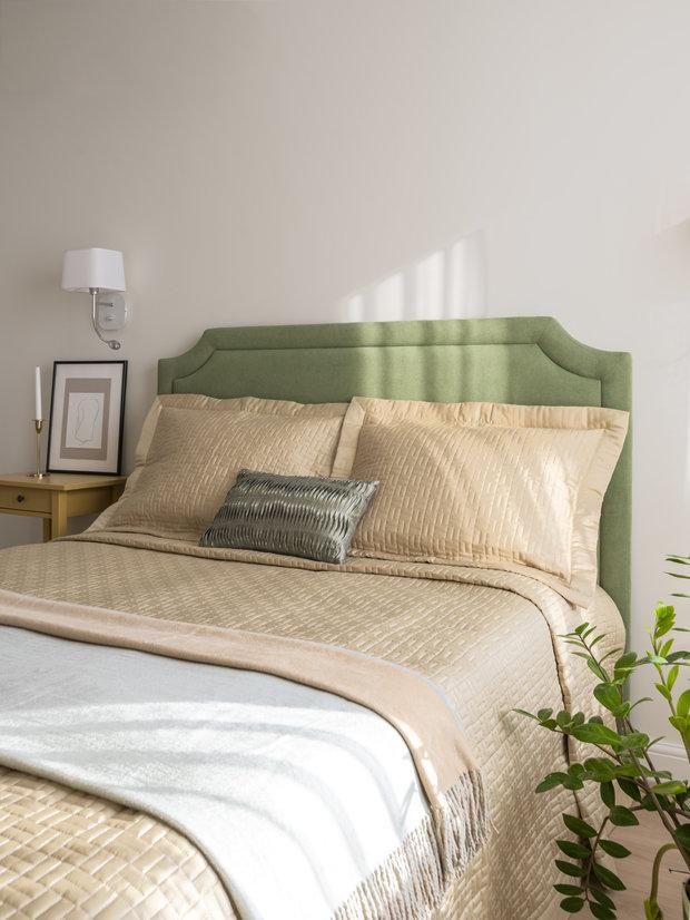 Акцентное зеленое изголовье отлично вписалось в нейтральную обстановку спальни.