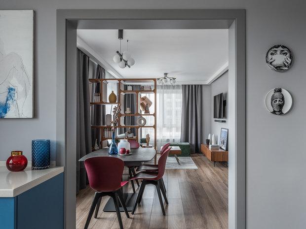 Дизайнер разбавила серый фон ярким синим кухонным гарнитуром и вишневыми стульями в столовой.