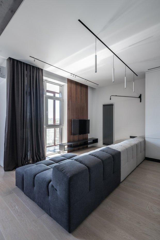 Не обошлось в квартире из без брендовых «точек притяжения». Одна из таких — диван Interia, расположенный вдоль всей зоны гостиной. Минималистичный дизайн, стык контрастных цветов — все его черты повторяют визуальную концепцию квартиры в целом.