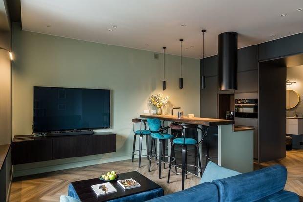 Остров играет роль зонирования, зрительно делит пространство на кухню и гостиную. Из-за приличных размеров он стал альтернативой обеденному столу и вмещает четырех человек.