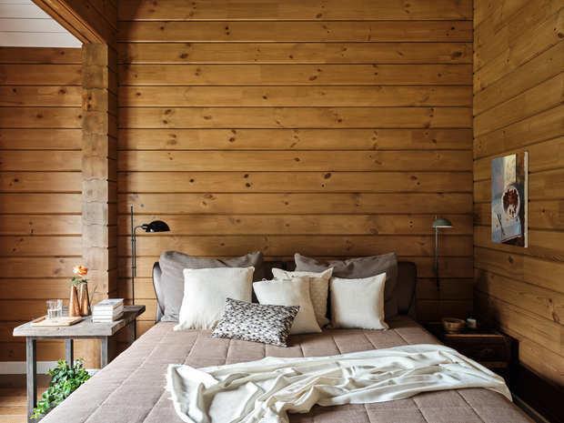 В мастер-спальне удачно соседствуют современная кровать в обивке из экокожи и прикроватные тумбы, сделанные на заказ частным мастером.