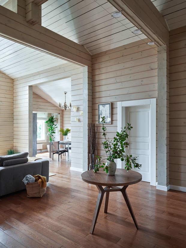 В проекте учтены как пожелания владельца, мечтавшего жить в деревянном доме, так и его супруги, которой хотелось получить интерьер в современном стиле. Их светлую цветовую палитру разбавляют яркие акценты в текстиле, коврах и декоре.