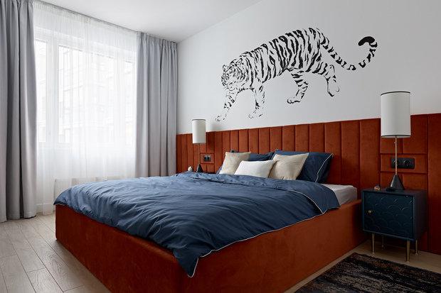 Мягкое изголовье кровати цвета тигровой шкуры создает уют, несмотря на яркость.