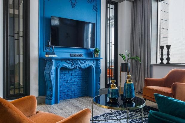 Акцент всей квартиры — это декоративный камин сложного синего цвета. Элементы лепнины выполнены локально.