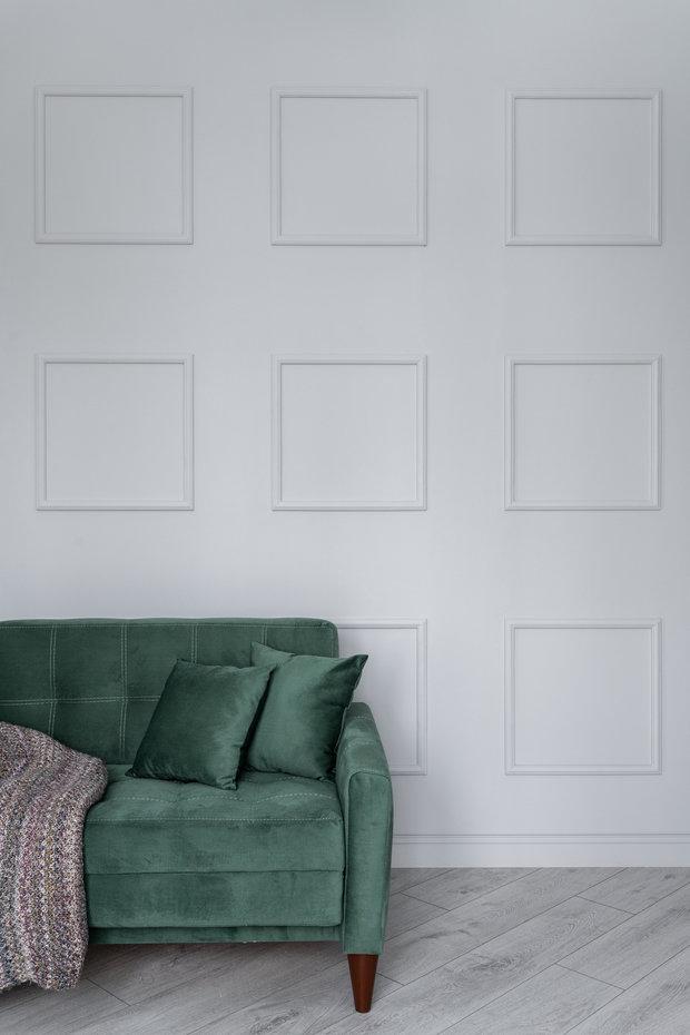 Стену за диваном украсили квадратами из молдингов.