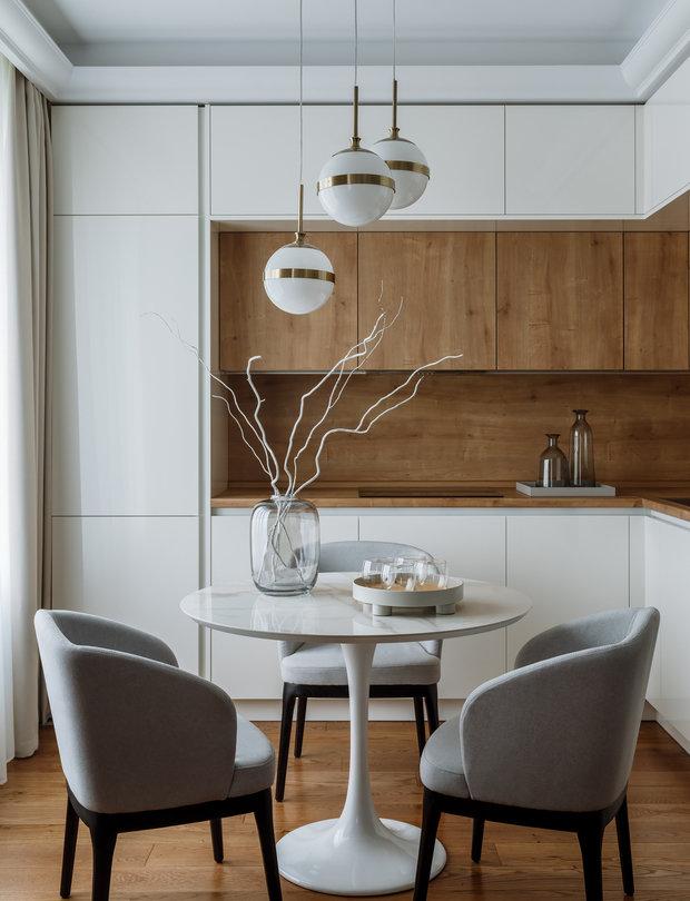 В отделке кухни сочетали белые фасады и под дерево.