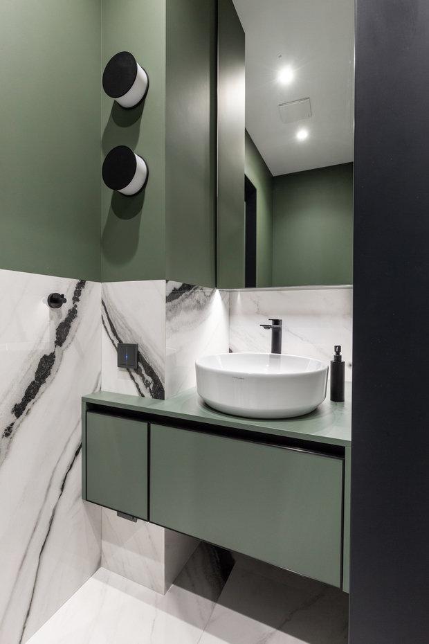Гостевой санузел оформили с использованием фактуры мрамора, сложного серо-зеленого цвета и черных элементов.