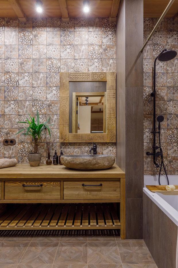 Зеркало ручной работы в сочетании с раковиной из речного камня сделали комнату по-настоящему необычной.