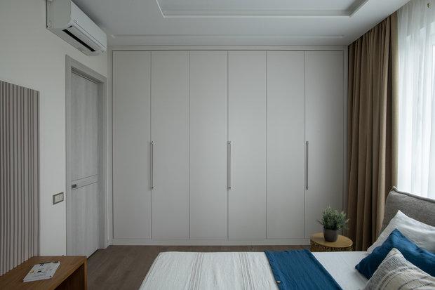 В спальне шкаф сделан без антресоли и выкрашен в цвет стен, чтобы максимально скрыть его.