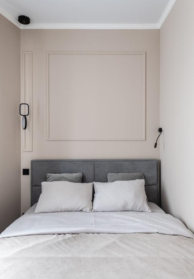 Дизайнер подчеркнула асимметрию комнаты раскладкой молдингов в изголовье и разными светильниками с двух сторон от кровати.