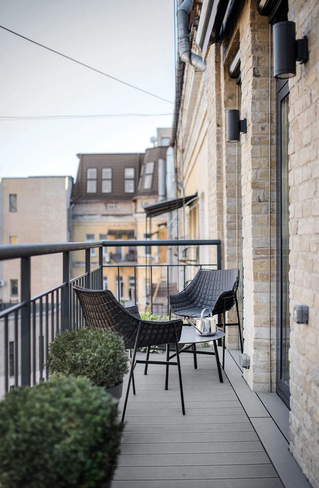 Еще вариант вечнозеленого, неприхотливого кустарника для балкона - самшит. Несколько одинаковых кашпо с этими растениями поддержали сдержанный дизайн и вытянутую планировку балкона студии в Киеве по дизайну бюро 2B.group.