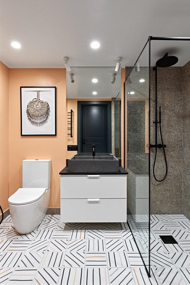 Рыже-персиковые стены в санузле добавили теплоты в строгий образ и расслабили ванную комнату.