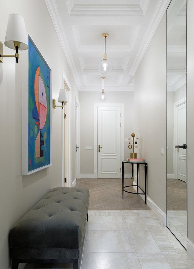 Особое внимание в интерьере коридора уделяется потолку, выполненному в виде кессонов. Этот прием позволяет приблизить вытянутую форму коридора к более пропорциональной.