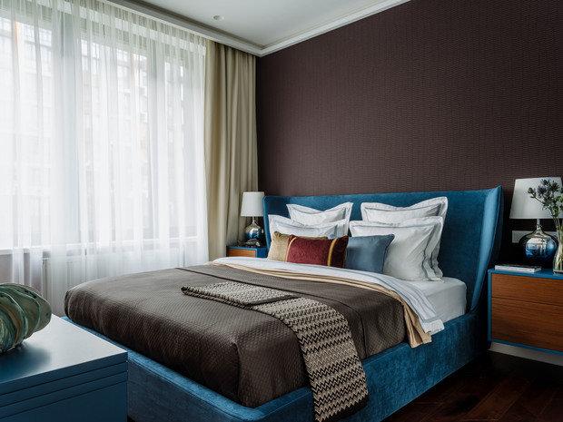 В спальне использовали темные обои с фактурой ткани и современным орнаментом, стилизованным под рисунок древесины.