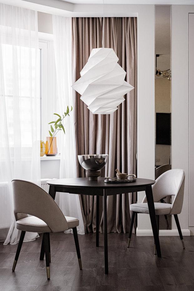 Самый завораживающий и приковывающий взгляд элемент в кухне-гостиной — люстра Artemide, которая была создана по мотивам культовой одежды Issey miyake и напоминает оригами.