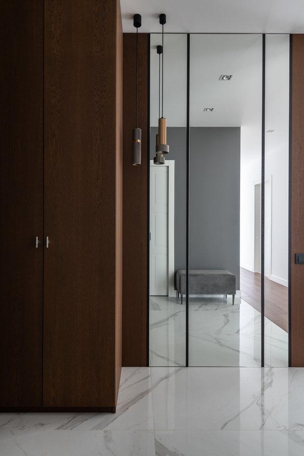 В прихожей создан ритм из стеновых панелей и зеркал, которые чередуются через черный профиль.