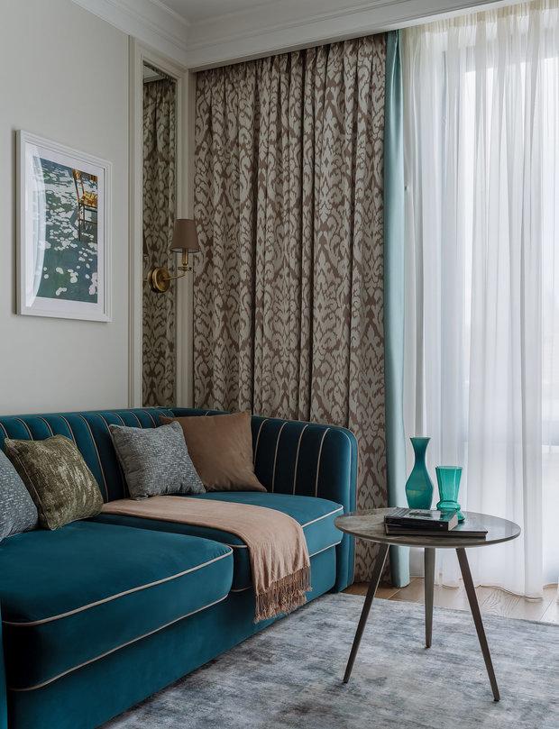 Диван насыщенного бирюзового цвета отлично смотрится со шторами и текстилем бежевого и кофейного оттенков.