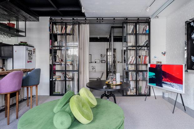 Между общей и приватной зонами предусмотрена металлическая перегородка со стеклами и открытыми стеллажами для книг.